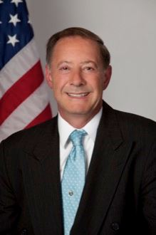 An official photograph of Assessor Gary P. Raupp, in front of a U.S. flag, wearing a light blue tie.