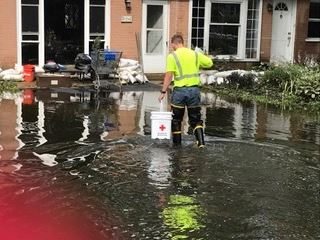 A worker in safety gear carries a bucket through a flooded area towards a building.